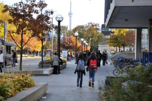 Two female student walking on campus. The CN tower can seen in the background.