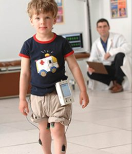 A young boy is walking with monitors on his leg. A doctor can be seen in the distance.