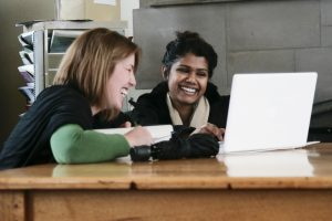 two female students smile looking at a laptop computer