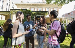 Four international students chat ourside a campus building