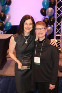 Kelly O'Brien holds OPA award, standing with Nancy Salbach