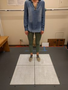 A patient stands on squares that measure balance.