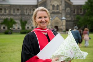 Gail Teachman at convocation, in her robes holding flowers.