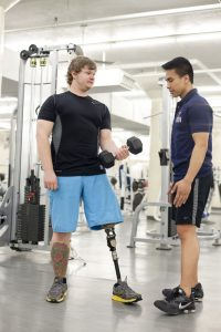 student with prosthetic leg lifting weights with a personal trainer