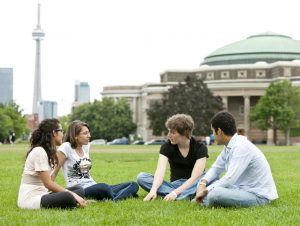 4 students, 2 female/2male, sitting on grass on campus. The CN towner is off in the background.