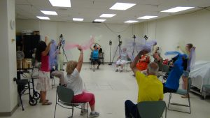 Stroke patietns sitting in a circle on chair, waving colourful scarves in the air to music