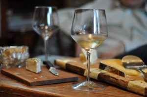 A glass of white wine sitting on a cheese board.